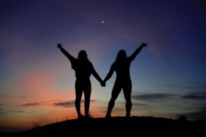 A stock photo of two people with their backs to the camera at dusk. We can see their silhouette against the sky, holding hands with their other hands raised.