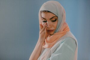 A woman wearing a hijab wiping the tears off her face.