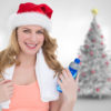 Festive fit blonde holding bottle of water against blurry christmas tree in room