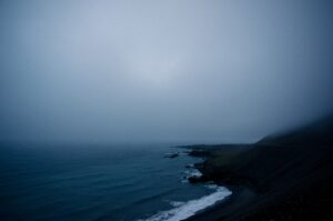 A dark and kind of gloomy photo of a cloudy rocky shoreline.