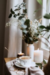 A stock photo showing a tabletop with a full teacup, a few lit candles, and a green bouquet in a white vase in front of a window.