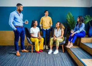 A stock photo of a group of people sitting in a colorful room.