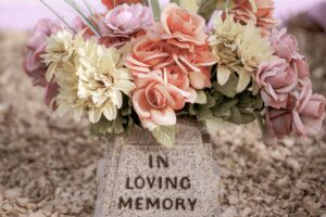 """A stock photo of a bouquet of flowers on a stone monument that says """"In Loving Memory""""."""