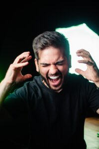 photo of a man in a dark room, yelling in anger. His hands are raised on either side of his face.